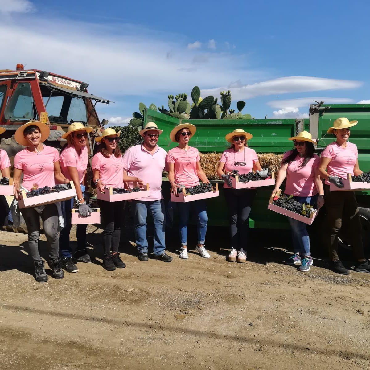 Foto di gruppo con tutto il team della vendemmia in rosa con le cassette piene d'uva.